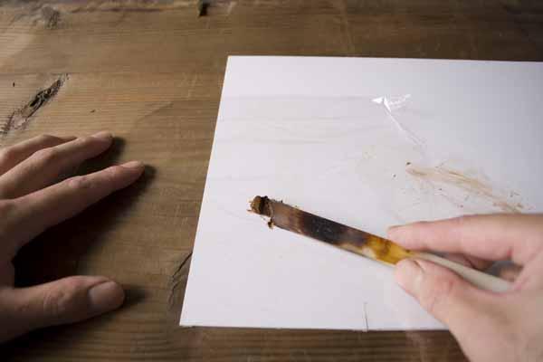 金継ぎで使う錆漆の作り方。箆を使って錆漆をサランラップの中央に載せます。