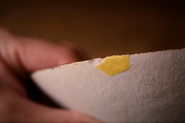 器の割れた個所にマスキングテープを貼っていく