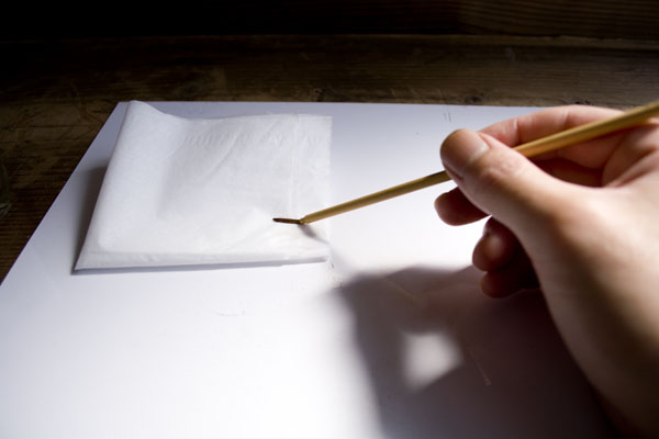 蒔絵作業で使った筆をティッシュの上できれいにする