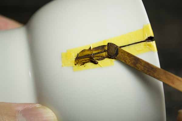 金継ぎのやり方。錆漆を載せたら、今度は箆で左右に均しつつ溝にしっかりと入れていきます。