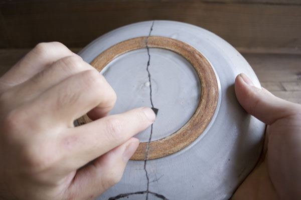 折り畳んだペーパーで水をつけならが漆を研いでいく。