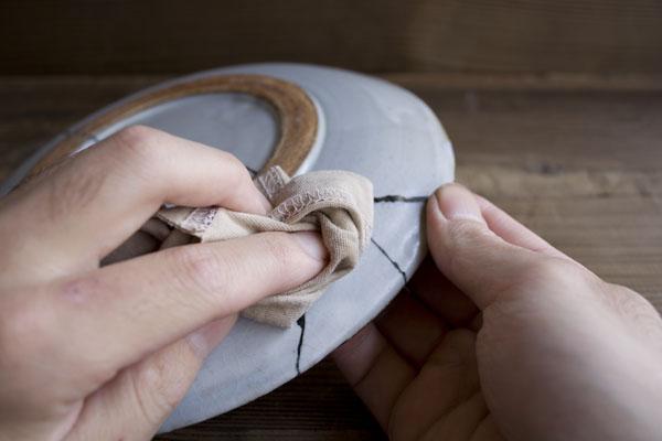 金継ぎの漆研ぎ作業では研いだ研ぎ汁をウエスで拭きとる。