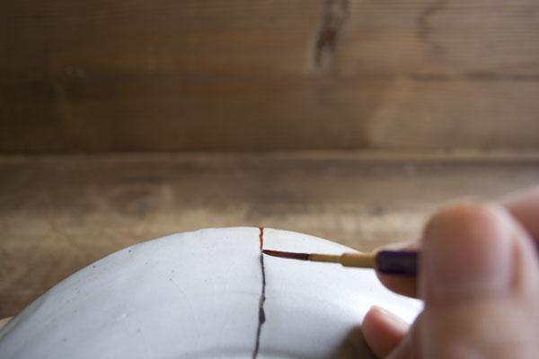 弁柄漆で金継ぎの上塗りを行う。なるべくはみ出さないように、均一の厚みに塗っていく。