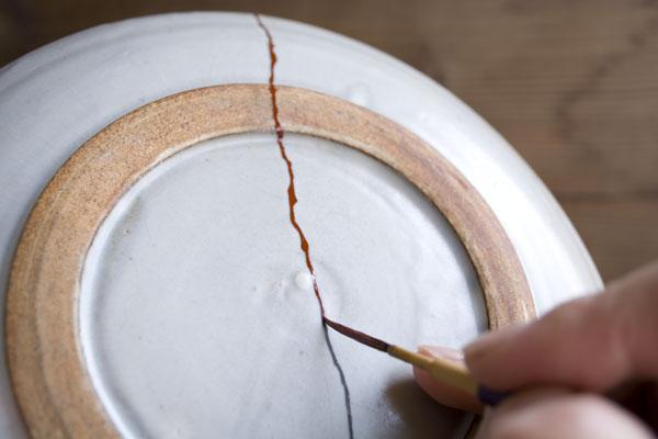 割れた器の継いだ部分に漆を塗っていく