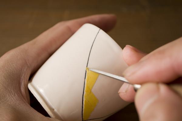 器の割れたラインに沿ってマスキングテープを貼っていく