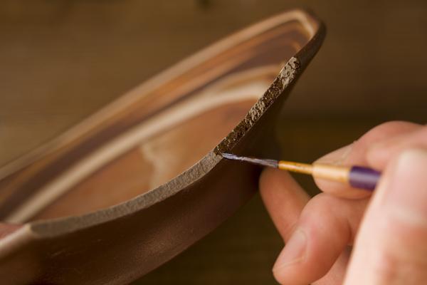 割れたお皿の断面に薄めた漆を塗っていく