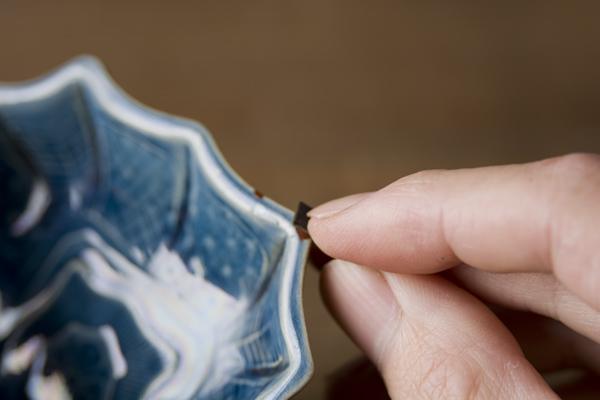 金継ぎの下塗り研ぎのやり方。ペーパーを三つに折り畳んで、指先でつまみながら研いでいく。