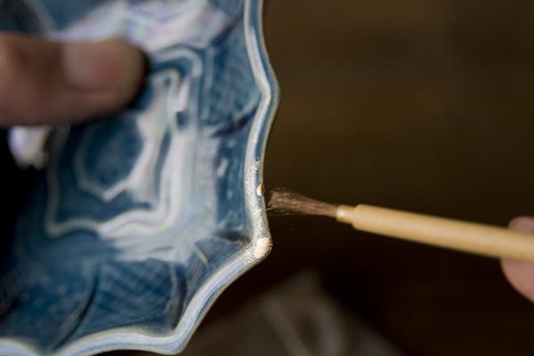 金継ぎの蒔絵工程を小さな欠けにも施した。小筆でササッと掃くように載せていく。