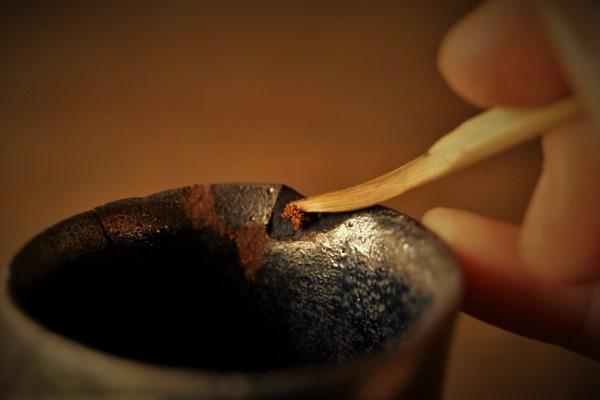 割れた器の金継ぎ方法。成形の必要な口元の欠け部分に刻苧を盛っていきます。