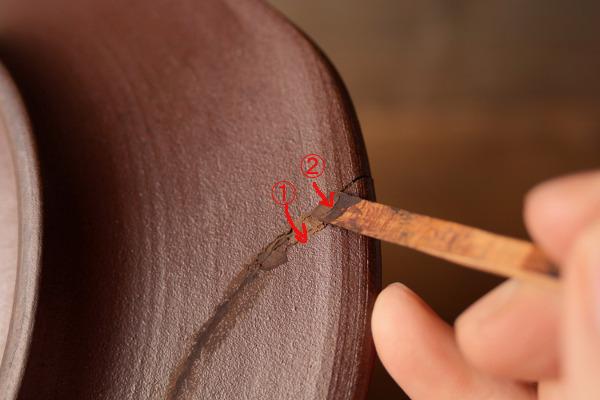 器の裏側も同様に行う。1,2と錆漆を付けた箆を接着ラインに対して直角に動かして、錆漆を隙間に入れていく