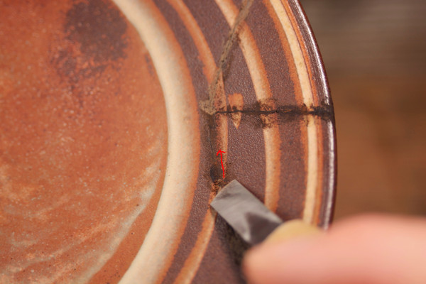 彫刻刀を矢印の方向に動かして錆漆を少しずつ削っていく