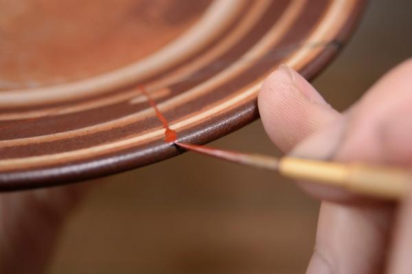 器の縁部分も塗り残しの内容に漆の上塗りを進めていく