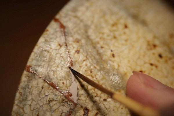 金継ぎの修理工程。蒔絵紛の固め作業。器の外側。