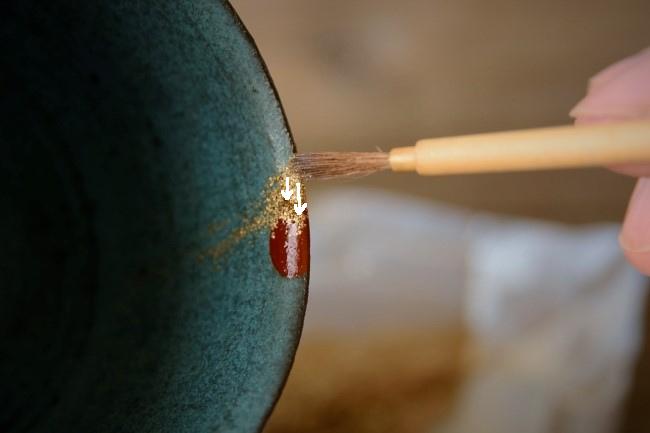 真鍮粉を筆で掃くようにして漆の上に移動させていく。
