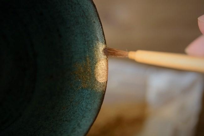 蒔絵の作業では筆で金属粉を払いながら漆の上にのせていく。