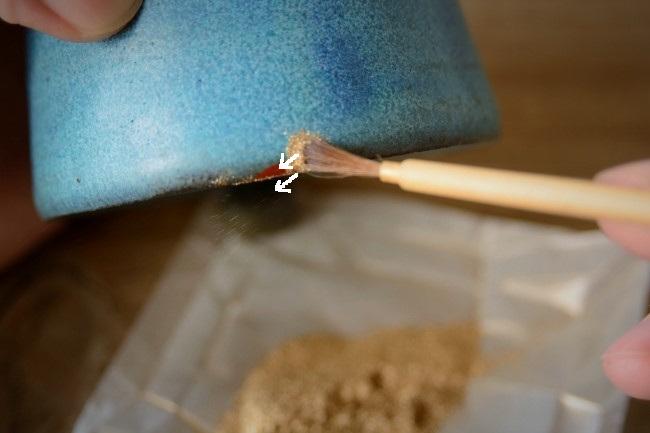 真鍮粉を筆で漆の上にのせて蒔いていく