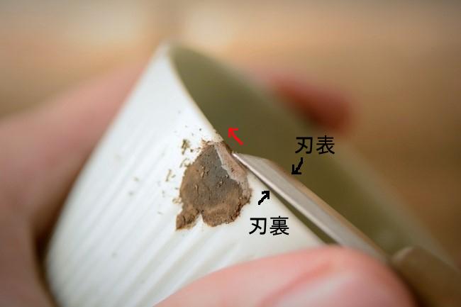 彫刻刀の一部を器に押し当てながら錆漆を削っていく