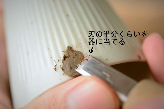 彫刻刀の刃裏の半分くらいを器に当てて、それをガイドにしながら錆漆を削っていく。