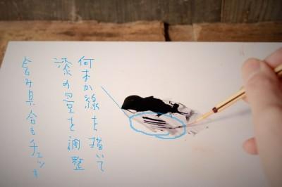 作業板の上で筆の中の漆の含み具合を調節する