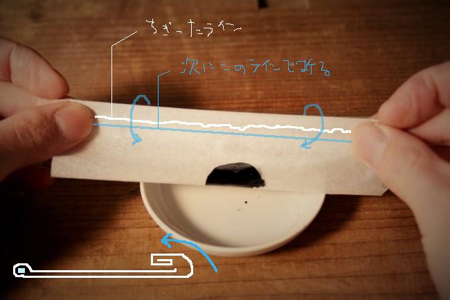 漆を入れた濾し紙を折り畳んでいく