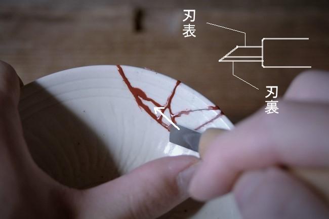 器の接着部分に盛ったエポキシペーストを彫刻刀で削っていく
