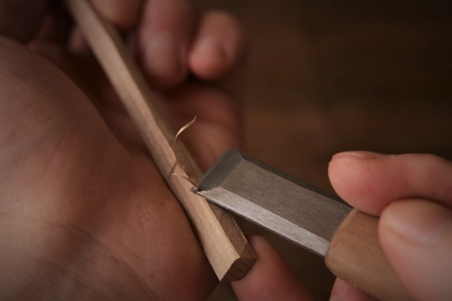 木工スプーンの柄の面を削る