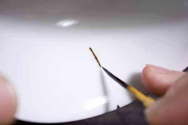 器の内側もひびに漆を浸み込ませていく。ひびの入った器の金継ぎ修理工程。
