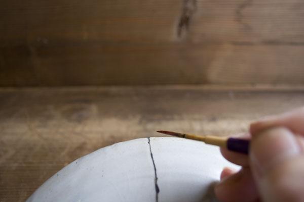 筆に漆を付けて器の継いだ部分を塗っていく