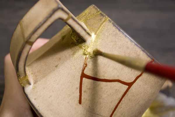 金継ぎの作業方法。柔らかい毛の筆を使って蒔絵をする