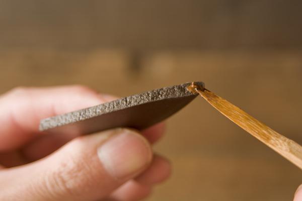割れた器のピースの断面にも麦漆を塗布していく