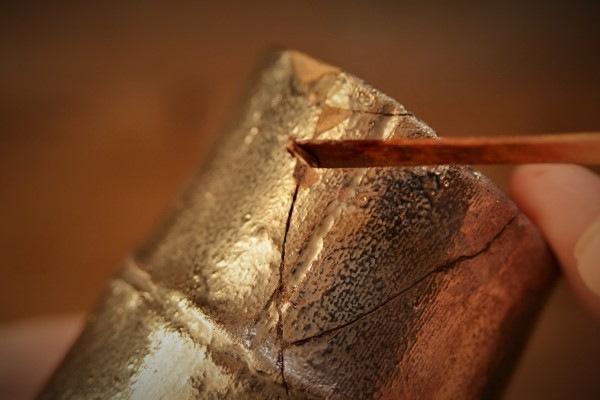 金継ぎの方法。錆漆を箆に付け、それを接着部分の溝に入れていく