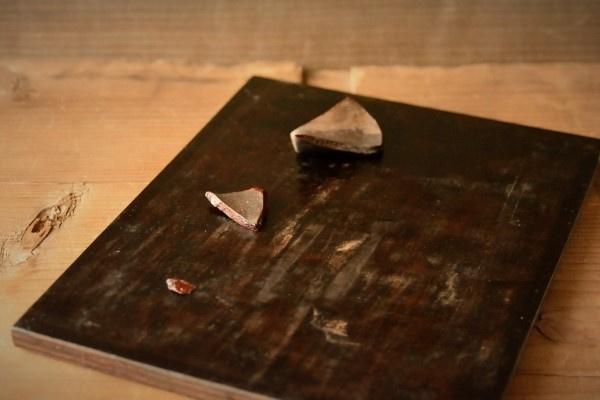 麦漆の塗布が完了した破片を持ち運びやすいように板の上に置く。