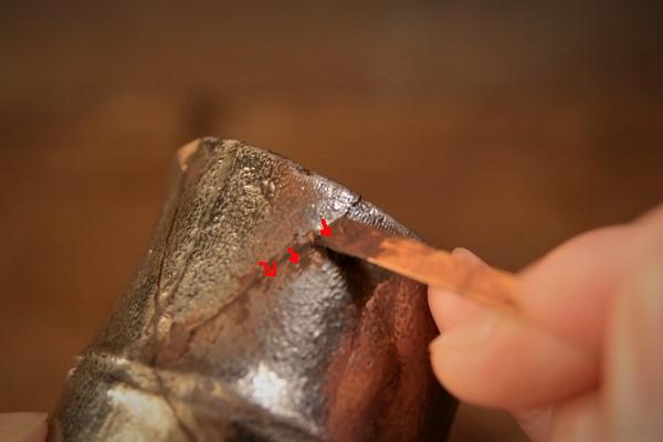 金継ぎの方法。続いてほかの接着ラインに錆漆を付けていく。はじめは直角気味に錆漆を付けていく。