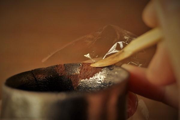 割れた器の金継ぎ方法。盛られた刻苧を箆で押し込んでいきます。