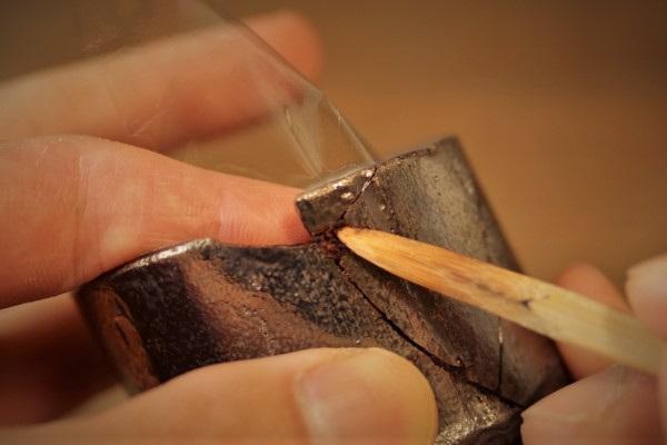 割れた器の金継ぎ修理。刻苧漆を盛ったら、刻苧箆で押さえる。