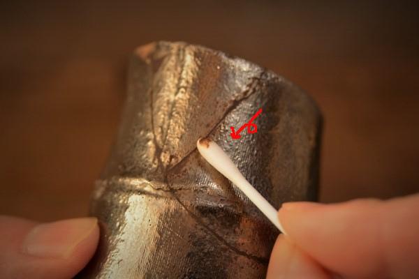 金継ぎの方法。錆漆の箆付けが終わったら、今度は綿棒で周辺についた錆漆をきれいに拭き取っていく。