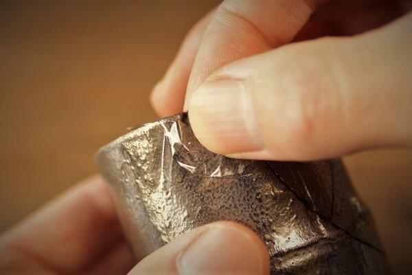 割れた器の金継ぎ方法。ぐるっとサランラップを内側から外側まで巻いてその上から指で押さえます。