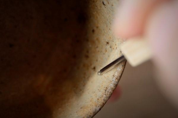 簡単金継ぎの修理工程。アームライトで手元を照らしながら器の内側のひびに沿って削っていく。