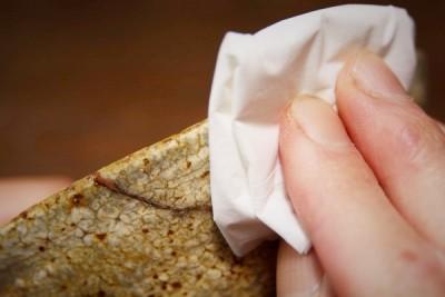 金継ぎのやり方。固めのために塗布した漆をティッシュで拭き取る。ティッシュを優しく押し当てる。
