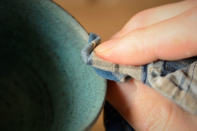 金継ぎの方法。ウエスで研ぎ汁を拭き取りつつ、錆漆の研ぎ具合をチェックする。慎重に研ぎ進める。