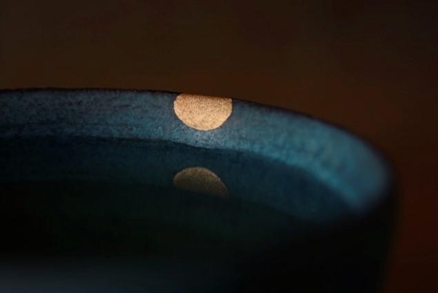 カップに水を入れて金継ぎ部分を水に反射させている