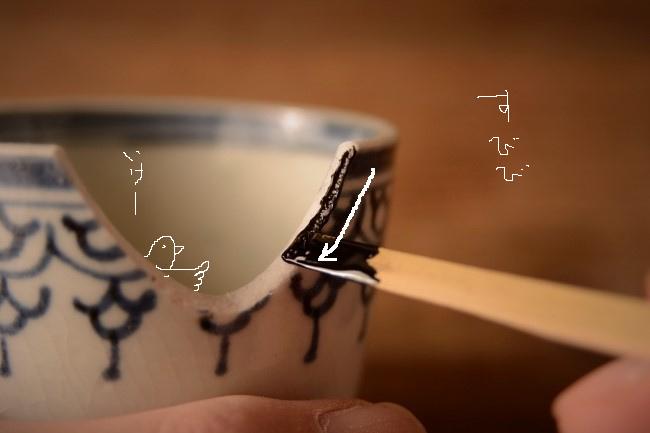 箆先に付けた接着剤を蕎麦猪口の割れた断面に薄く付けていく。