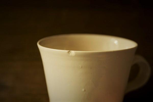 口元が欠けた岡田直人のマグカップ