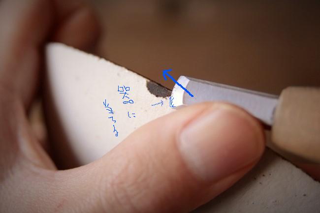 彫刻刀の刃裏を器に当てながら錆漆を削っていく