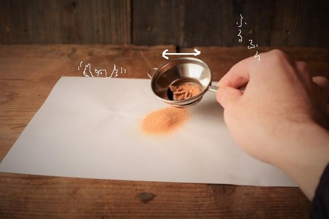 木粉の入った茶漉しを振るう