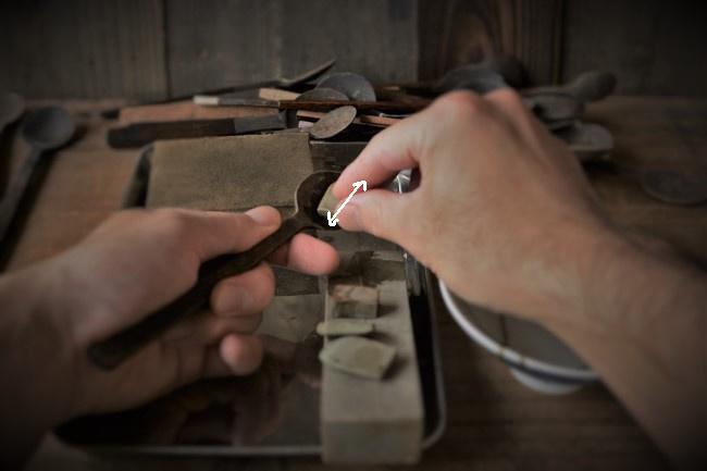 スプーンに付けた錆漆を砥石で研ぐ